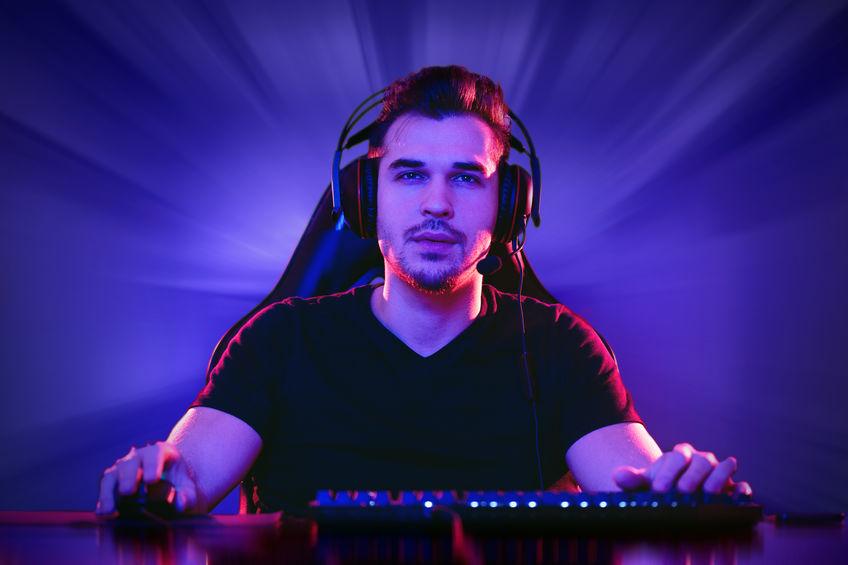 Imagem mostra um homem, de frente para a câmera, jogando um jogo e usando cadeira gamer, headset, mouse, teclado e mouse pad, todos do tipo gamer.