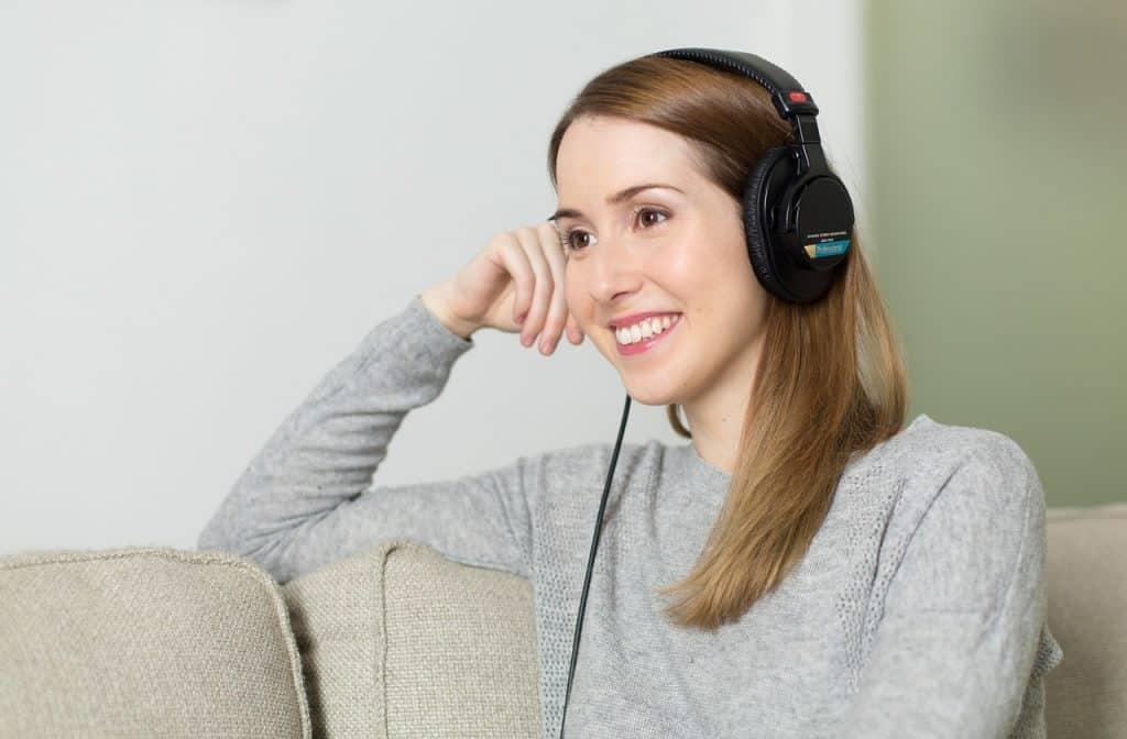 Imagem de uma garota sentada num sofá com fone de ouvido e sorrindo.