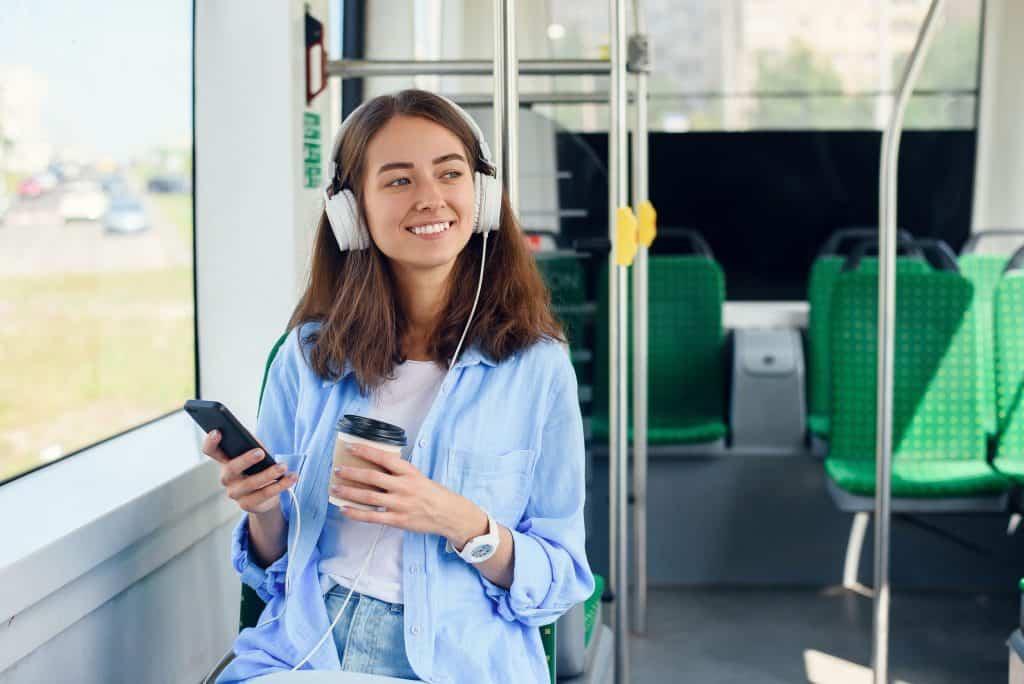Imagem de uma garota com fone de ouvido, um celular e um copo de café nas mãos.