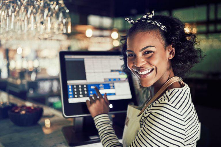Imagem de uma mulher usando um monitor touchscreen.