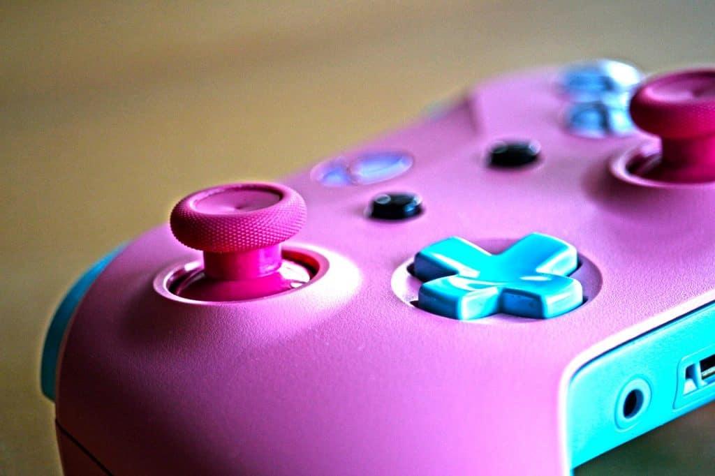 Imagem de controle de Xbox One cor de rosa com detalhes em azul.