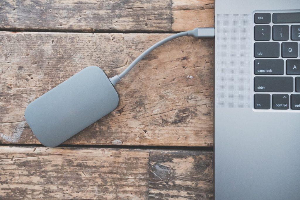 Imagem de HD externo cinza conectado a um notebook