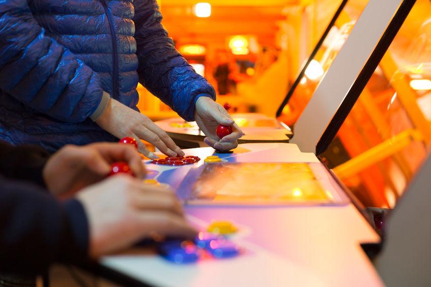 Imagem mostra um close das mãos de duas pessoas, manuseando os controles de um mesmo arcade.