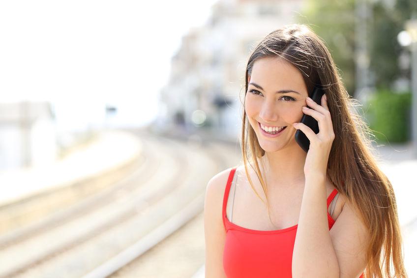 Mulher caminhando e falando em celular e sorrindo.