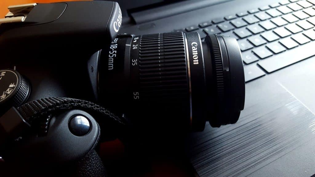 Imagem mostra uma câmera DSLR da Canon em cima do teclado de um computador.