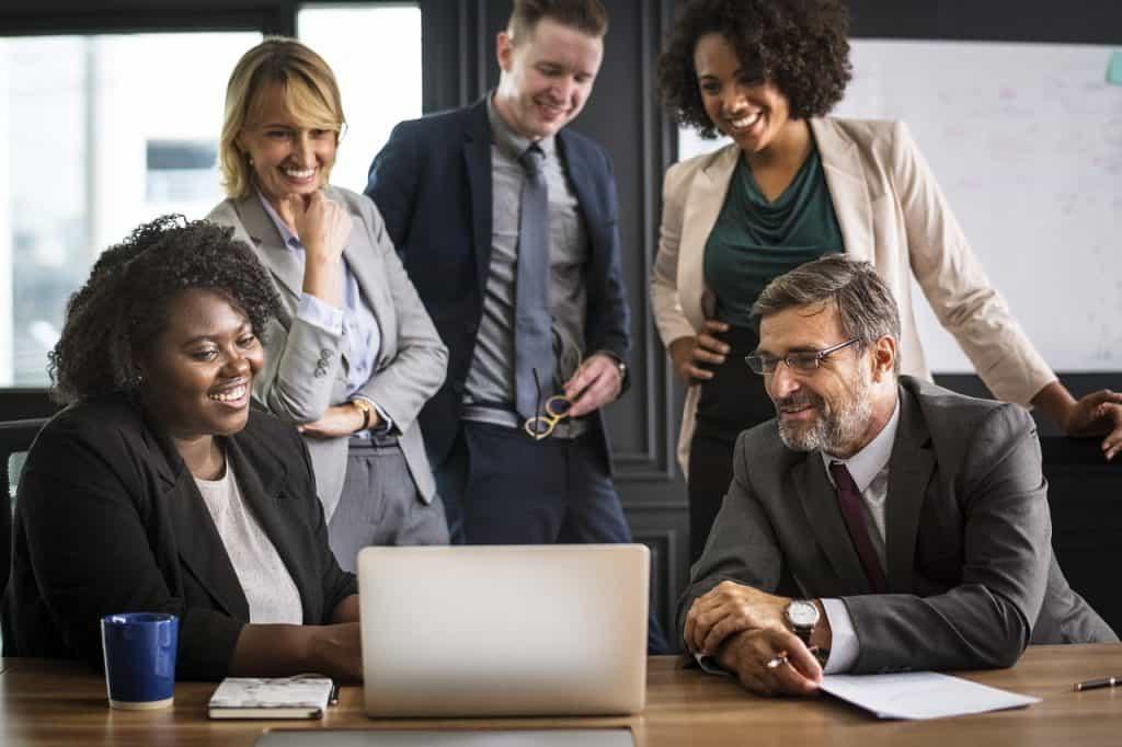 Três homens e duas mulheres com trajes executivos sorriem olhando para notebook sobre a mesa.
