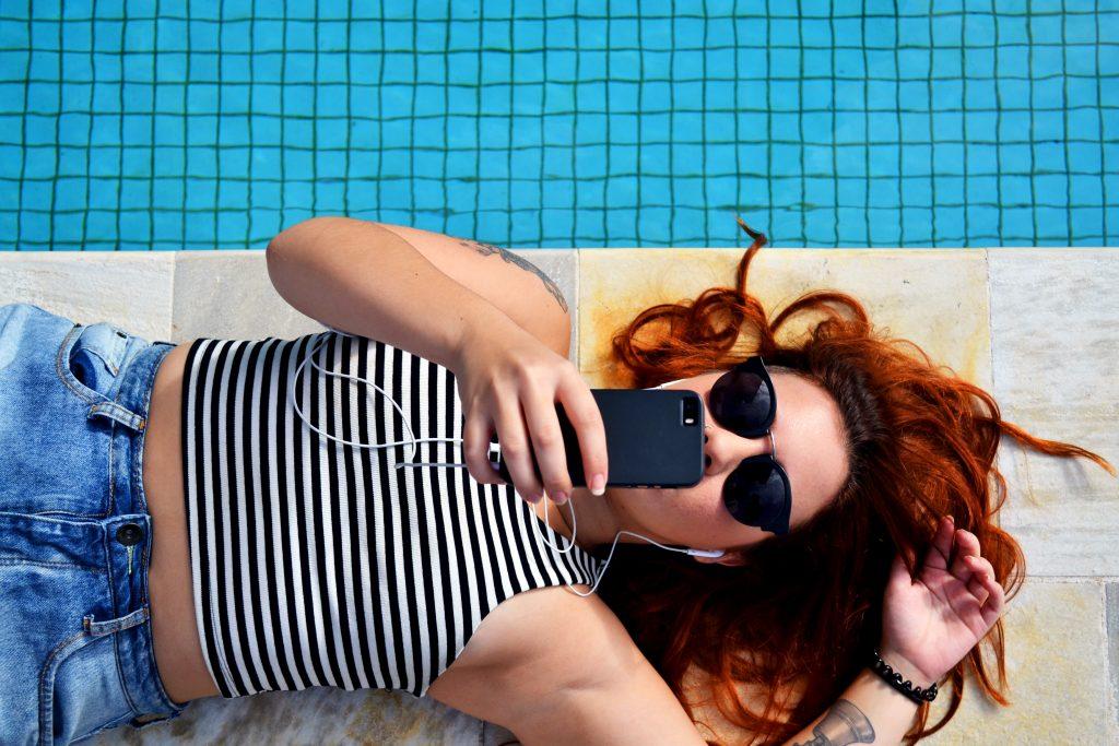Imagem mostra uma mulher ouvindo algo no seu celular com um fone de ouvido, enquanto está deitada ao lado de uma piscina.