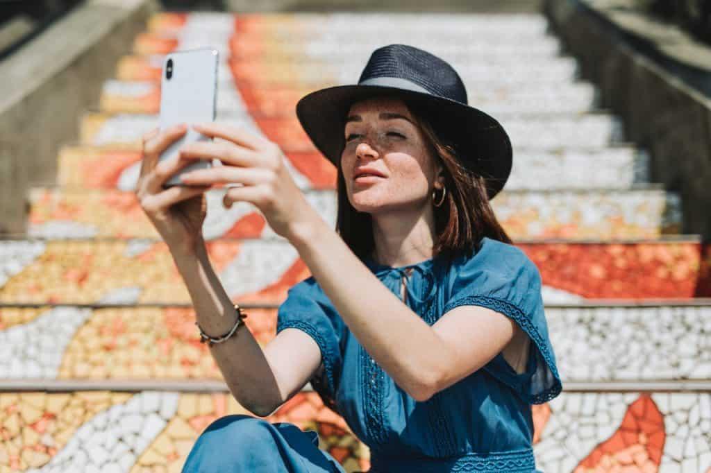 Imagem de uma moça tirando uma selfie com um iPhone X.