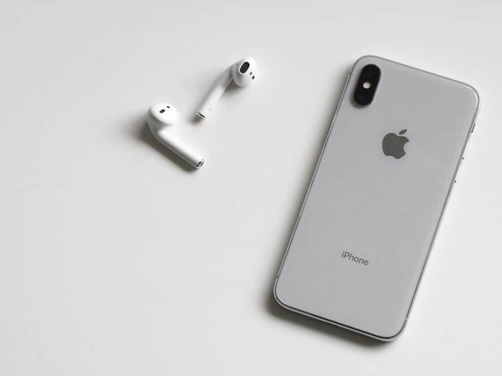 Imagem de um iPhone X ao lado de um par de EarPods.