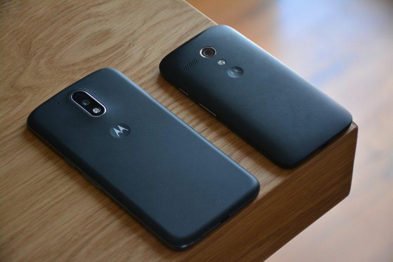 Dois aparelhos celulares da Motorola, um ao lado do outro, em cima da mesa.