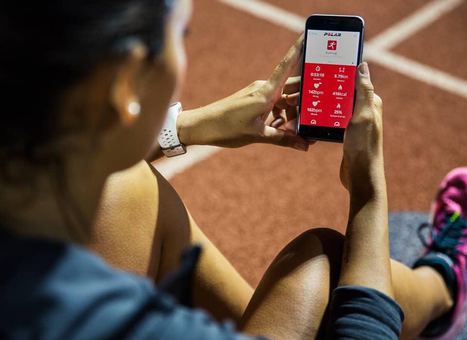 Imagem de pessoa com relógio polar M430 e celular com aplicativo vinculado.