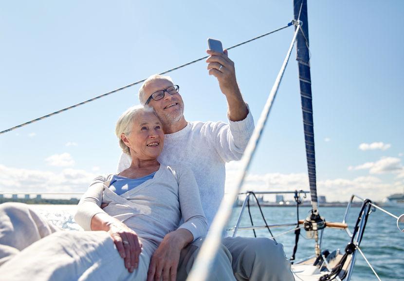 Casal idoso fazendo self em barco.