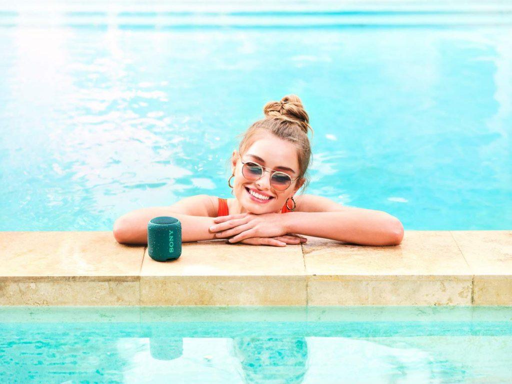 Na foto uma mulher dentro de uma piscina com uma caixa de som ao lado.