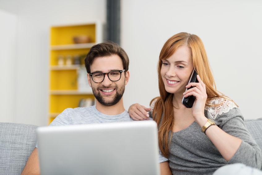Imagem de mulher sentada ao lado do esposo enquanto fala ao telefone