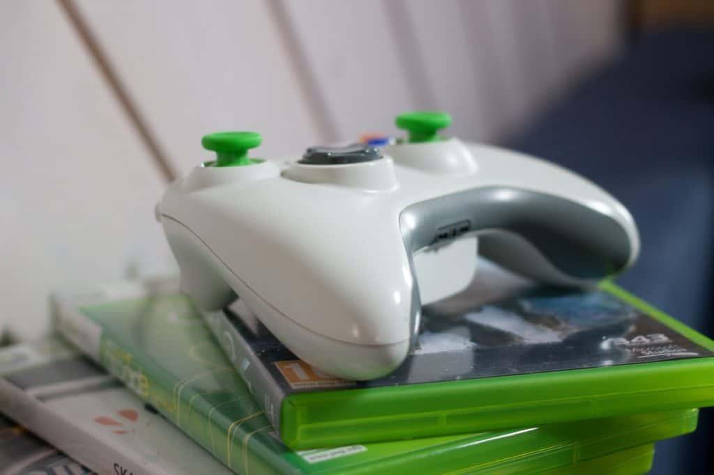 Imagem de controle de Xbox sobre uma pilha de jogos.