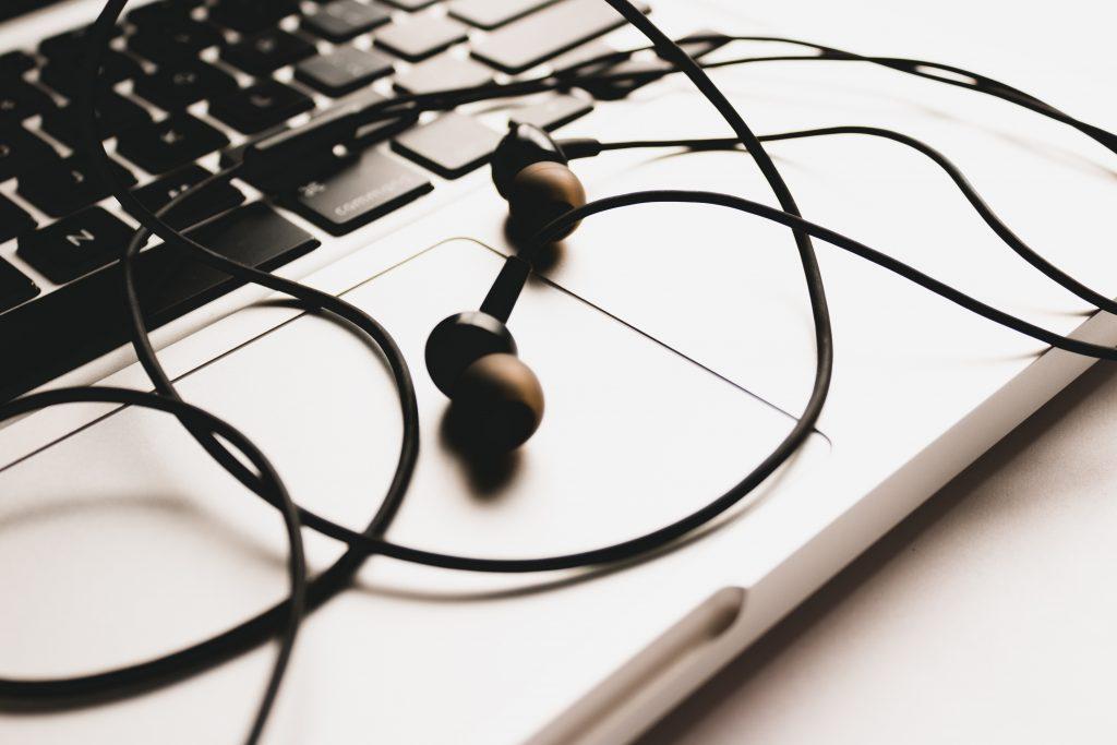 Imagem mostra um fone de ouvido do tipo intra-auricular apoiado sobre o mousepad de um notebook.