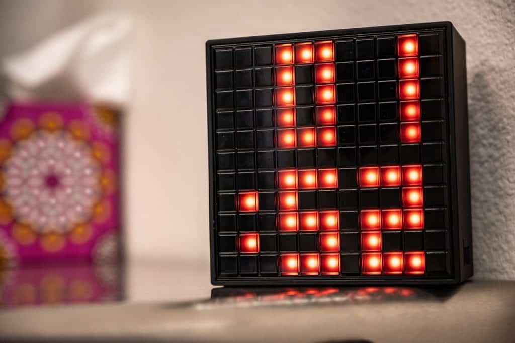Na foto um relógio digital preto com os números em vermelho.