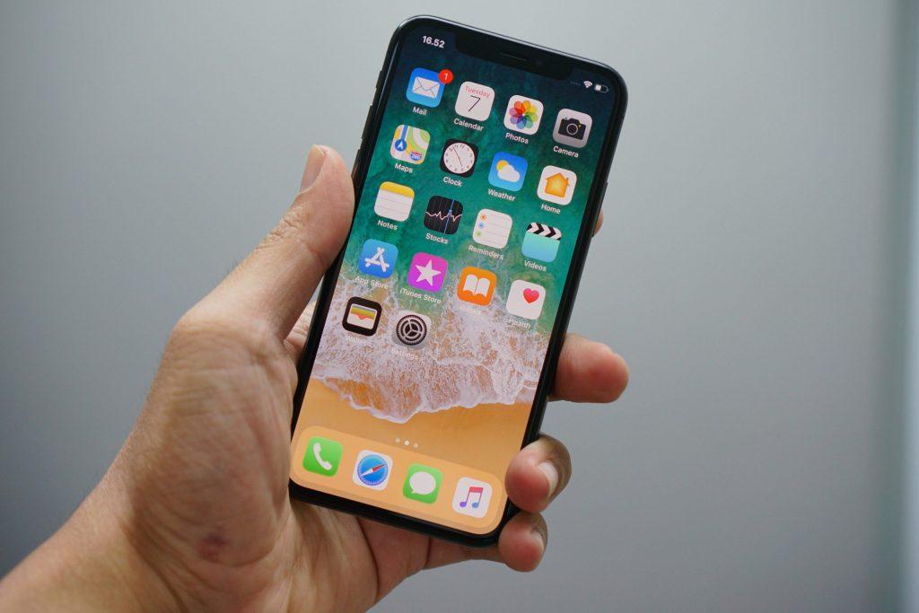 Mão masculina segurando um iPhone.
