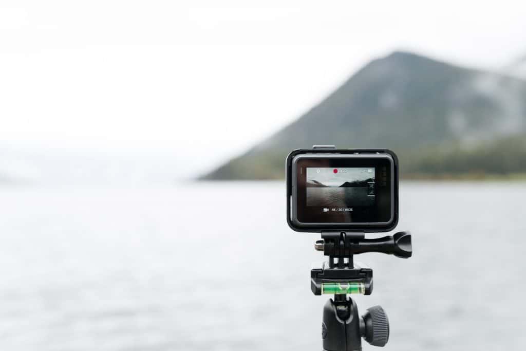 Na foto uma câmera GoPro em um tripé apontada para um mar.