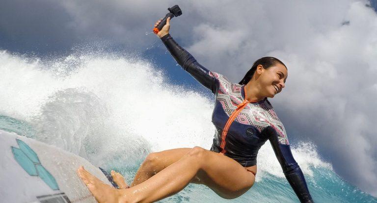 Menina surfando segurando uma GoPro com bastão The Handler.