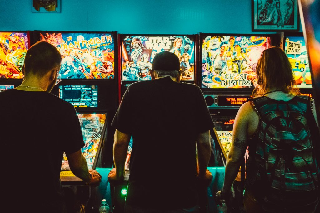 Imagem mostra três pessoas, de costas para a câmera, jogando em arcades clássicos.