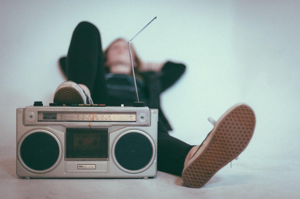 Imagem mostra uma mulher, em segundo plano, desfocada, deitada e com o pé direito apoiado num rádio antigo, este sim no foco seletivo, em primeiro plano.