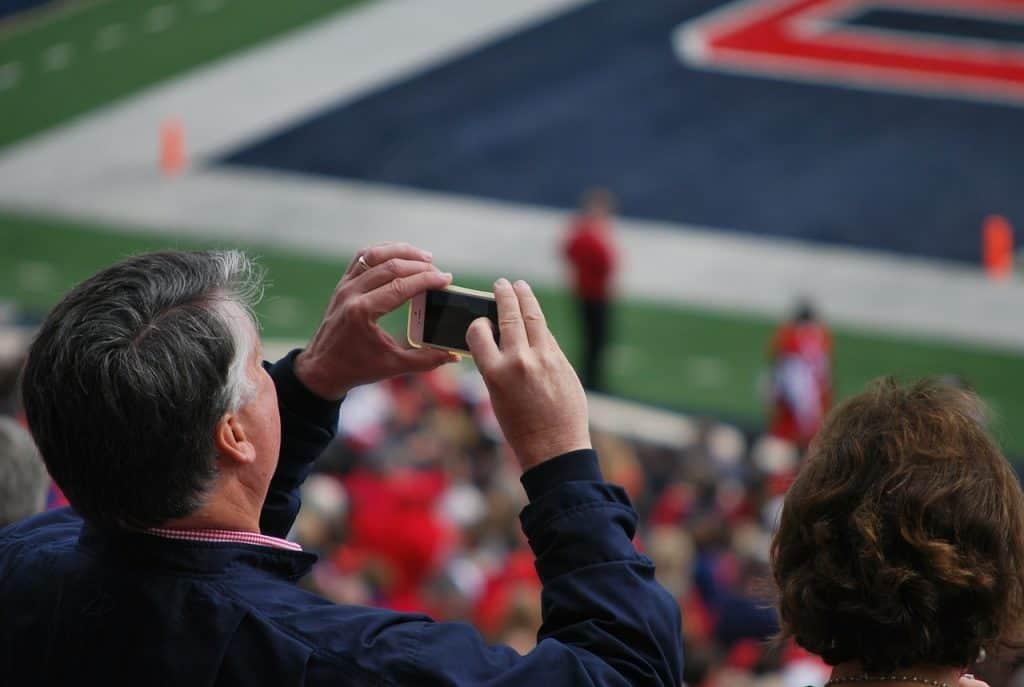 Na foto um homem tirando uma foto com o seu iPhone em um estádio.