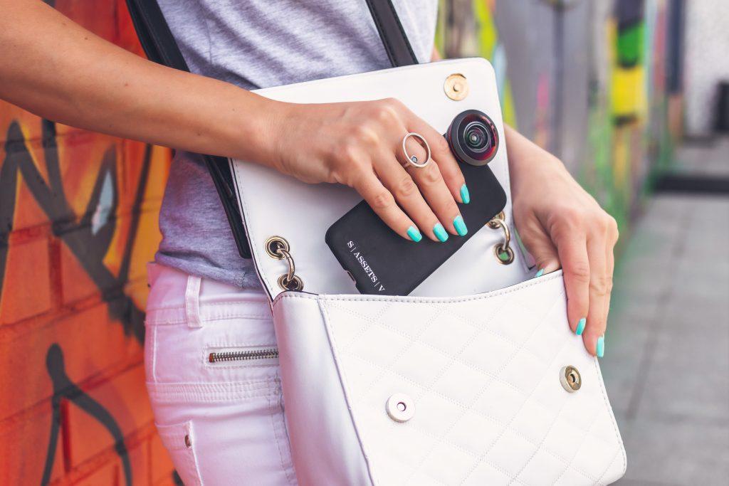 Imagem de uma mulher guardando o celular na bolsa.