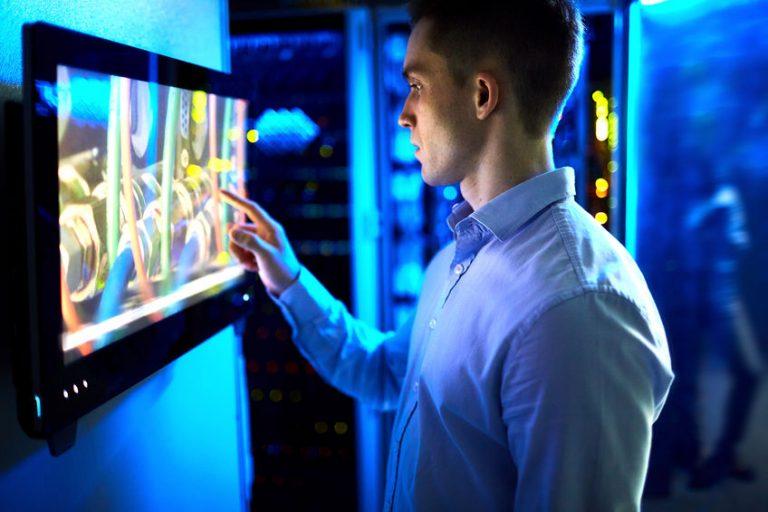 Imagem de um homem usando um monitor touchscreen.