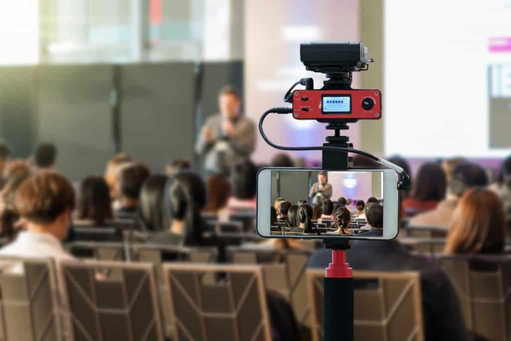 Na foto um monopé com um celular com a câmera virada para uma sala de aula.