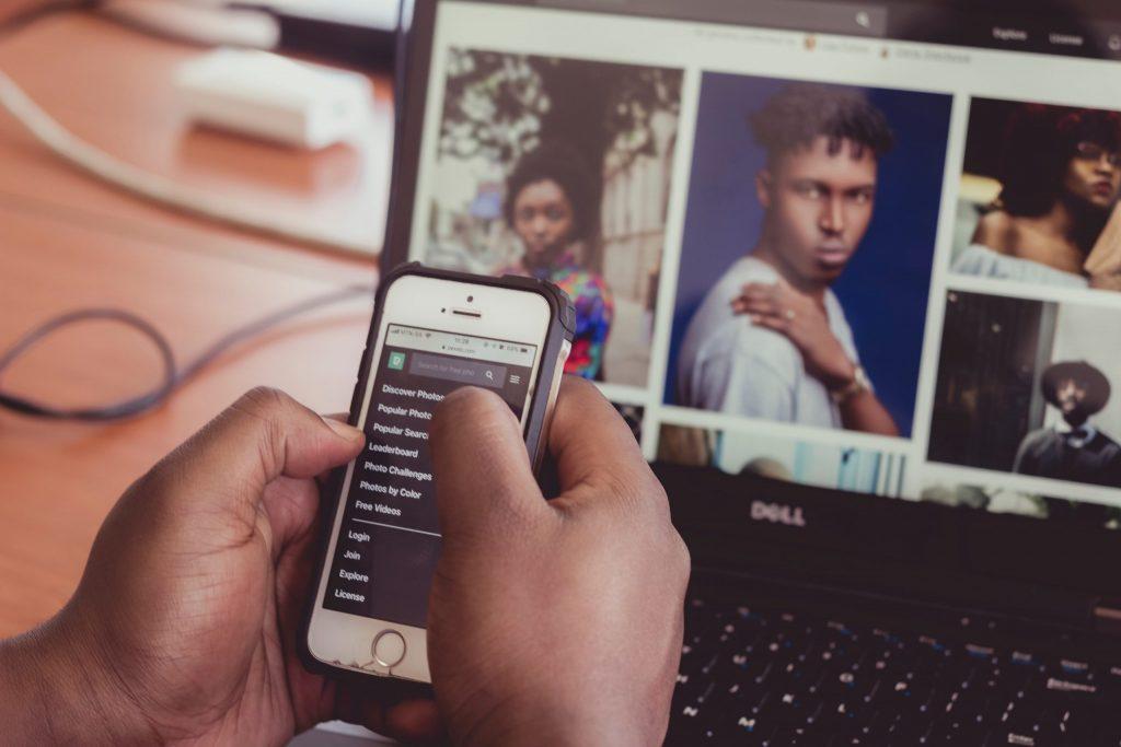 Homem manuseando o celular com notebook ao fundo com fotos na tela.