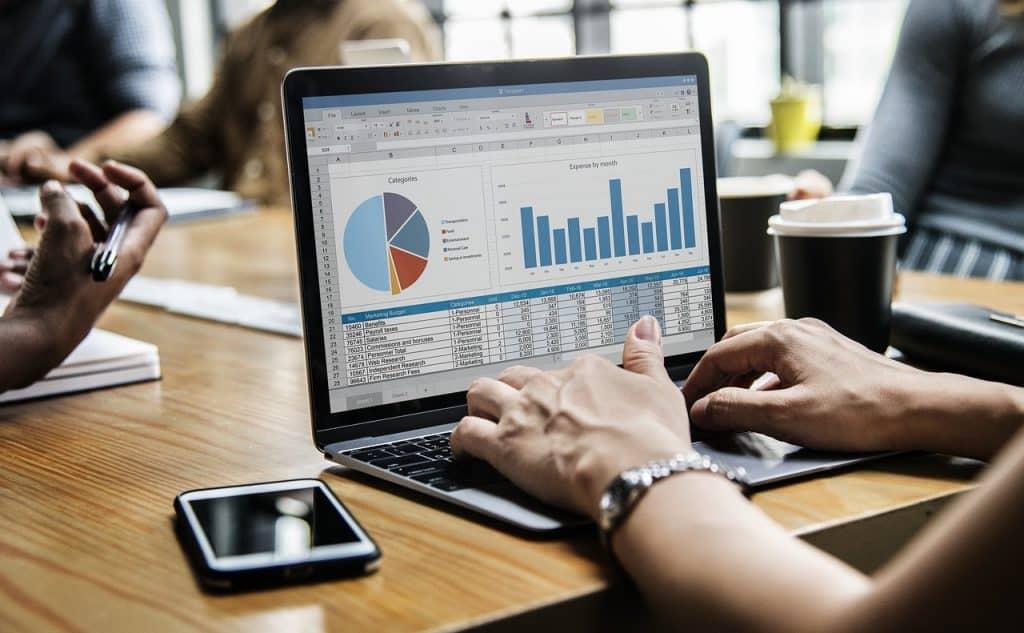 Imagem de pessoa trabalhando em um notebook em uma sala de reunião.