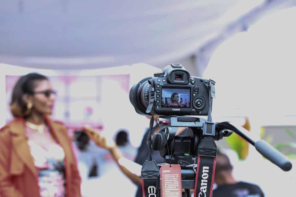 Na foto uma câmera gravando uma mulher sendo entrevistada.