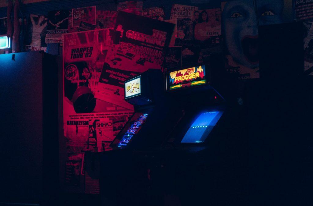 Imagem mostra dois arcades ligados num ambiente de luz baixa e papéis de parede decorativos.