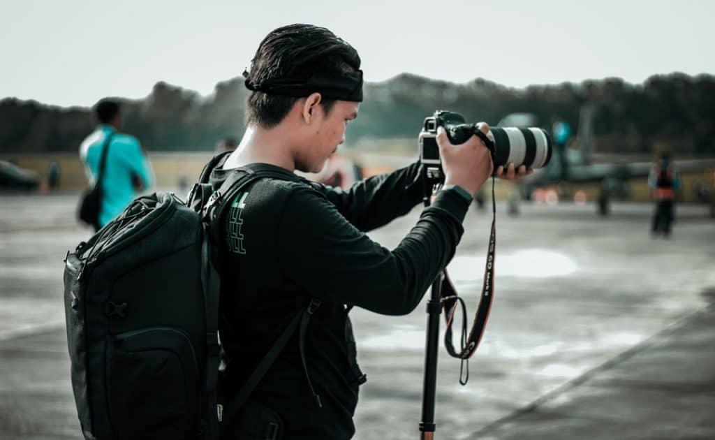 Na foto um fotógrafo com uma câmera colocada em um monopé.