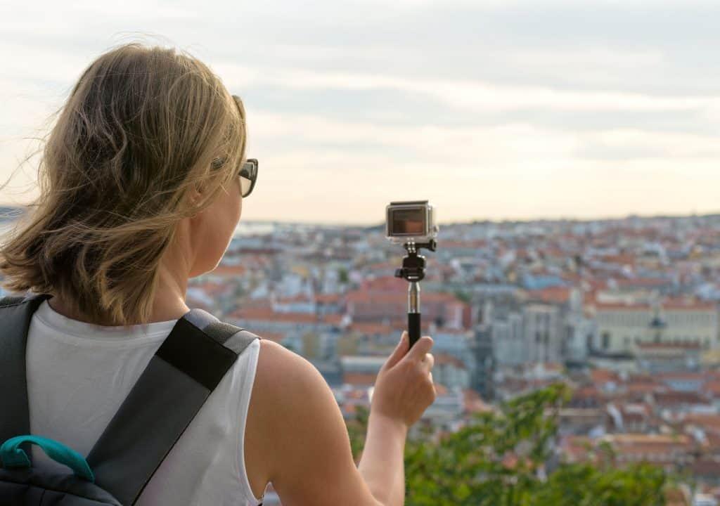 Na foto uma mulher de costas segurando um monopé com um GoPro apontado para uma cidade ao fundo.