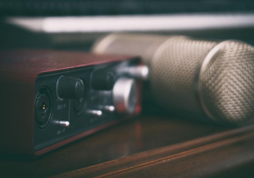 Imagem mostra uma placa de som USB ao lado de um microfone condensador.