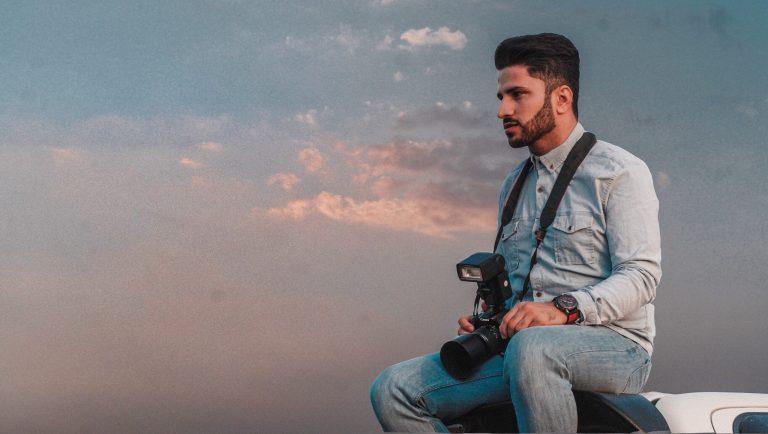 Homem com máquina fotográfica e flash.