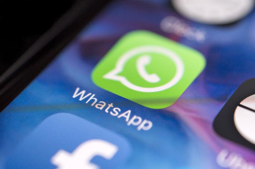 Tela de celular com foco em logo de aplicativo WhatsApp.