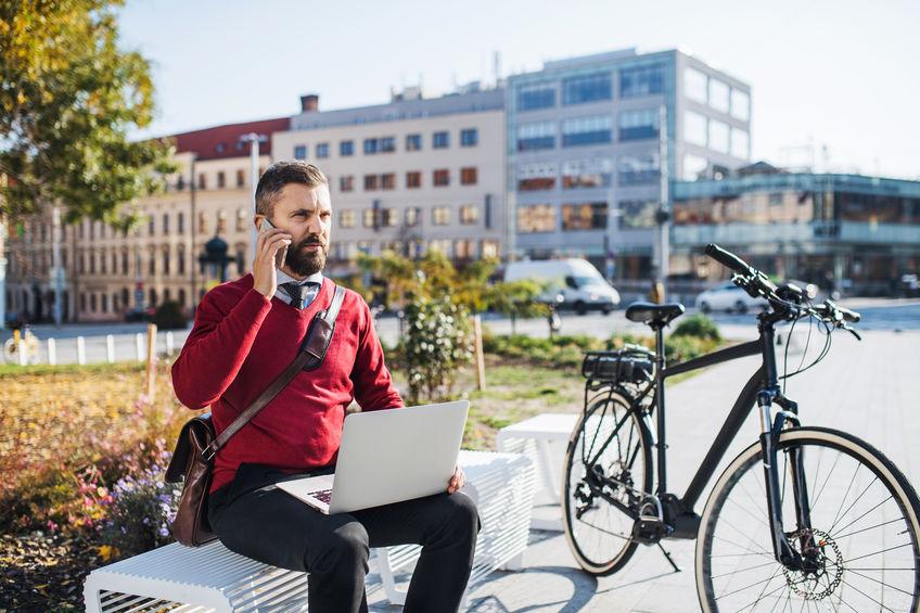 Homem sentado em banco ao ar livre ao lado de sua bicicleta mexendo em seu computador e falando ao celular.