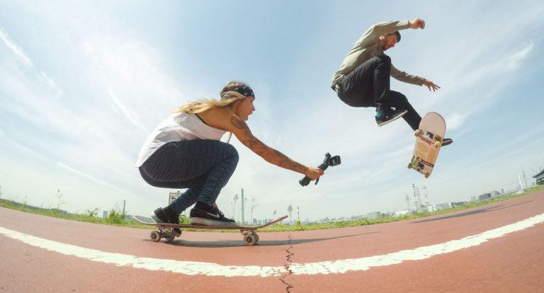 Menina de skate filmando outro skatista usando uma GoPro.