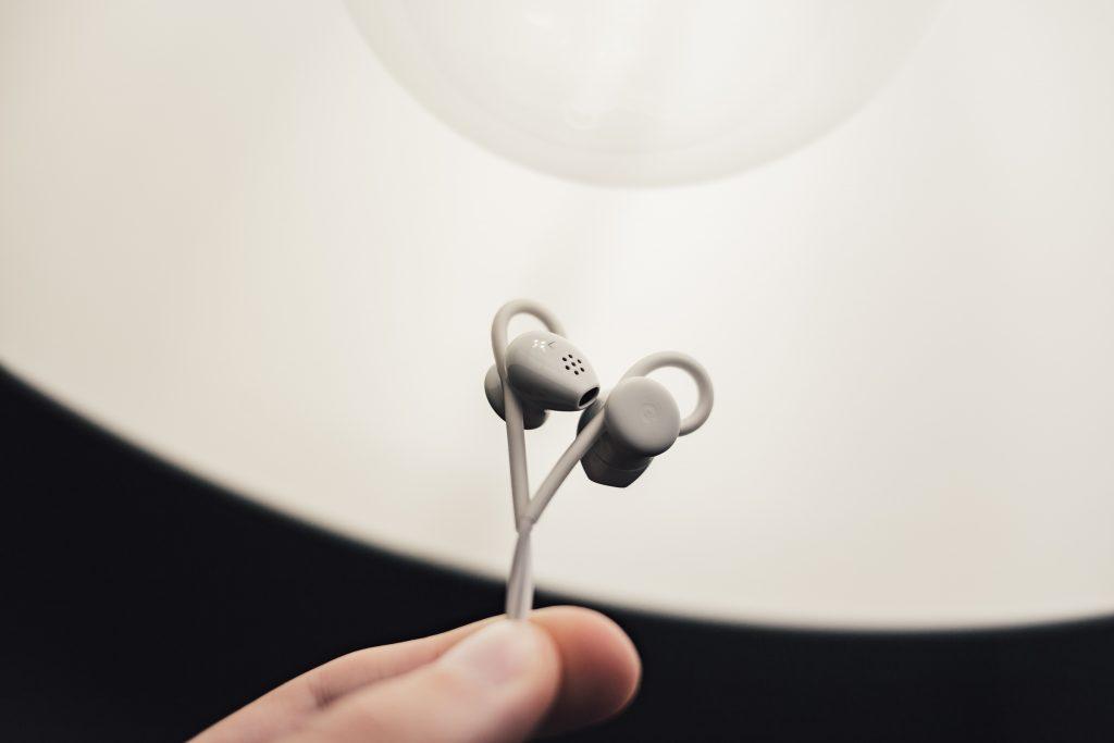 Imagem mostra dois dedos segurando a ponta de um fone de ouvido sobre uma pia de banheiro, desfocada.