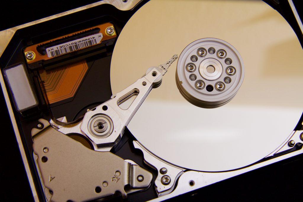 Imagem mostra o close da parte interna de um hd, focando o seu disco e no seu número de série.