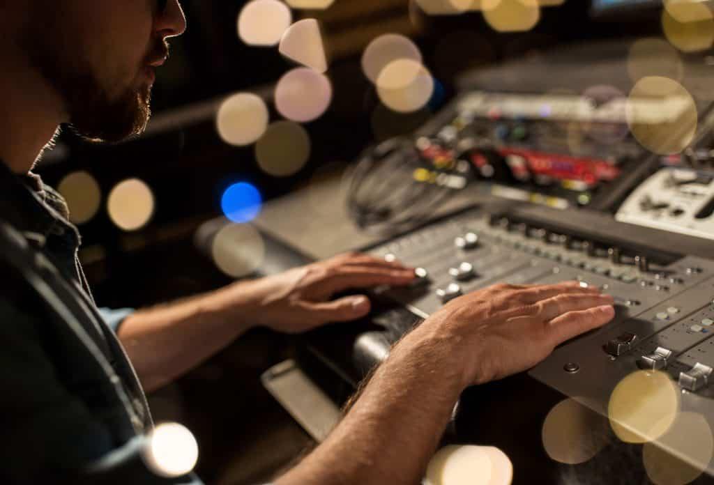 Imagem mostra um homem mexendo em uma mesa de som.