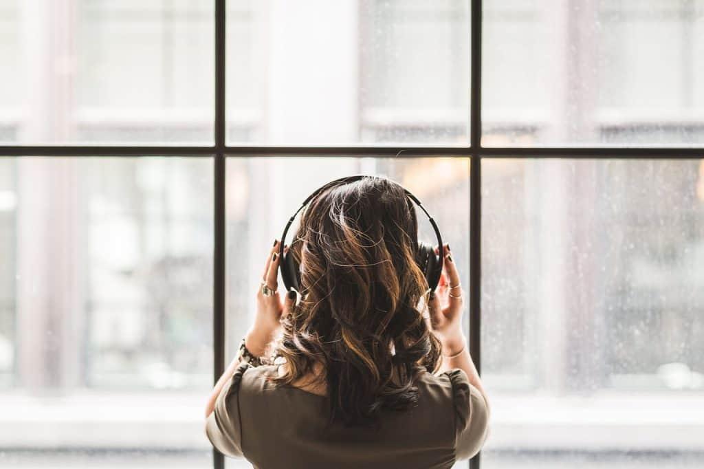 Na foto uma mulher de costas em frente a uma janela com um fone de ouvido.