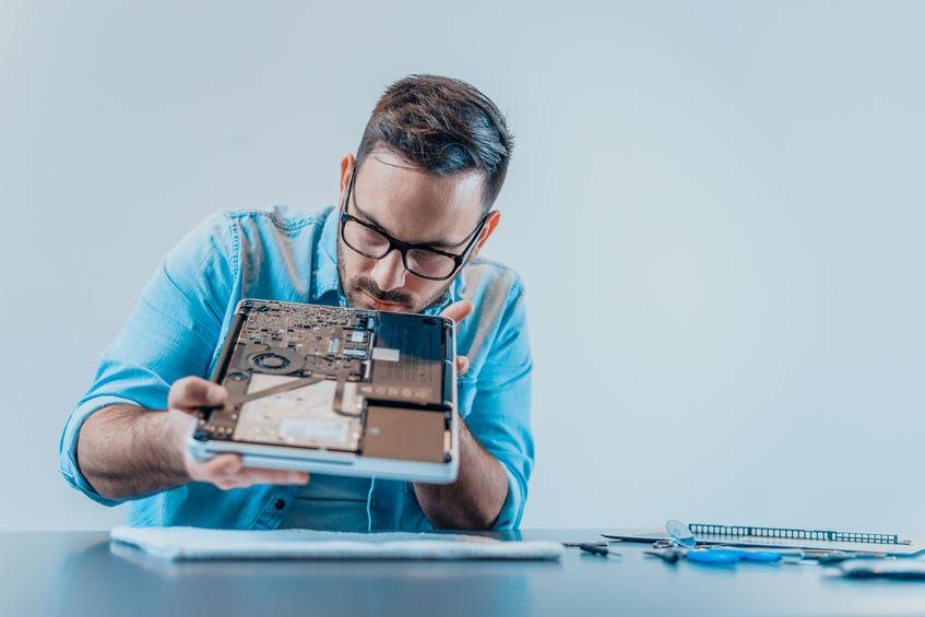 Homem examina componenetes interno de notebook desmontado