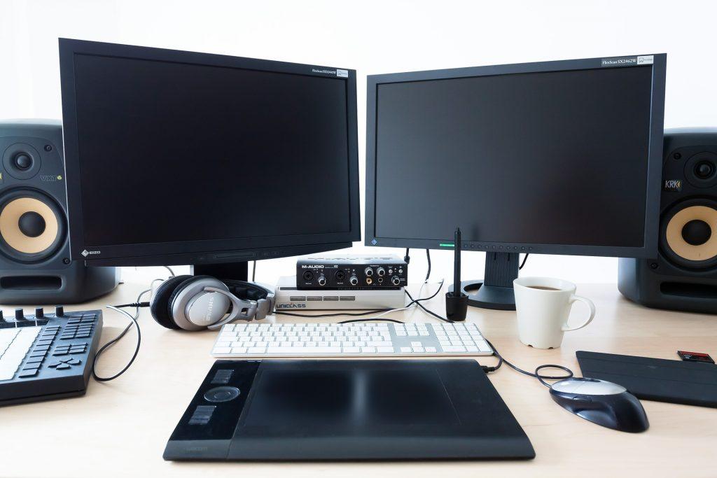 Dois monitores, teclado e caixas de som.
