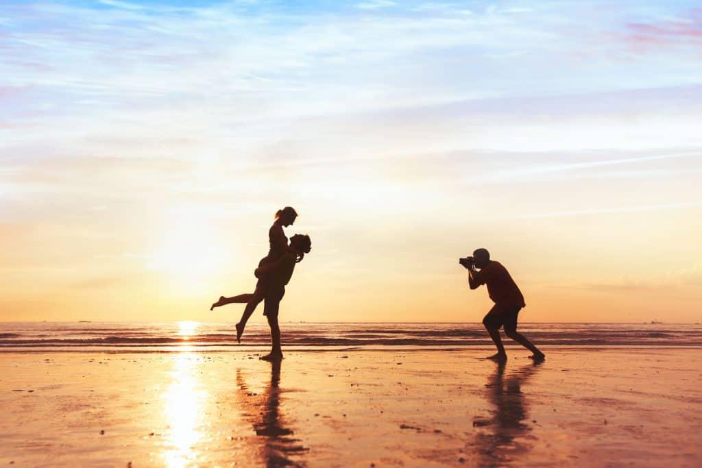 Na foto um fotógrafo tirando fotos de um casal em uma praia no pôr do sol.