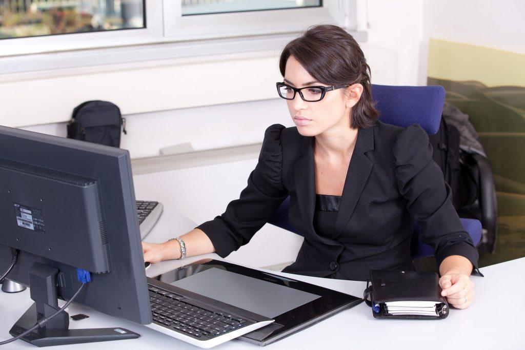 Mulher de frente para computador.