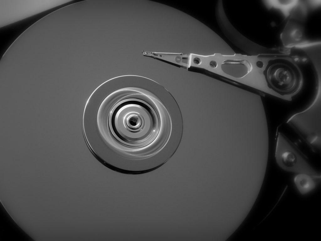 A imagem, em preto e branco, mostra, em close, um disco interno de um hd durante um giro.